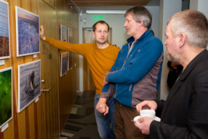 Näituse autorid, fotograafid Jarek Jõepera ja Kaido Haagen arutamas halllhülge pojaga foto ees koos hülgeuurija Ivar Jüssiga (keskel).